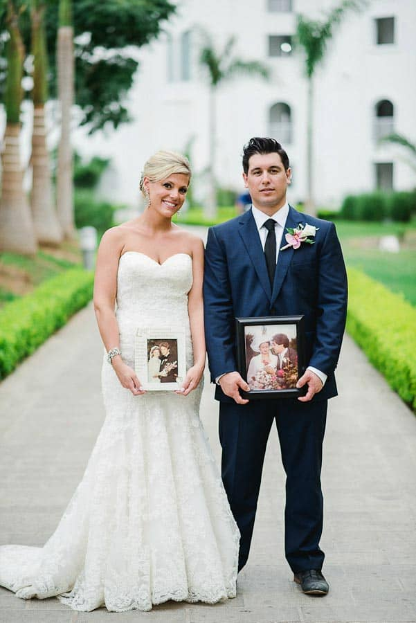 newlyweds holding photo of their parent's weddings