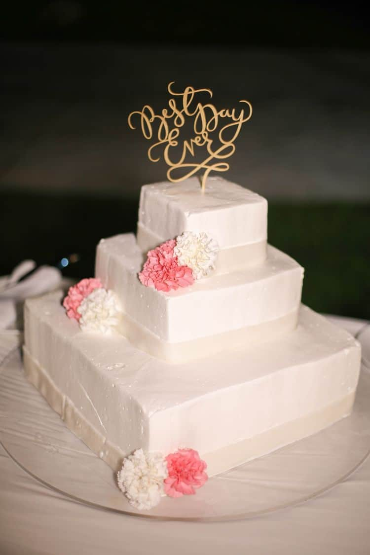 White beach wedding cake with pink and white peonies and gold topper