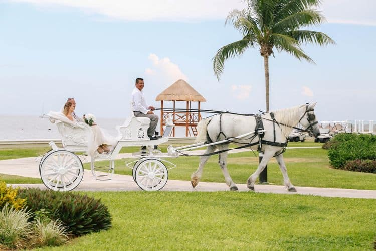 The bride arriving in a horse drawn carriage for her destination wedding at the Moon Palace
