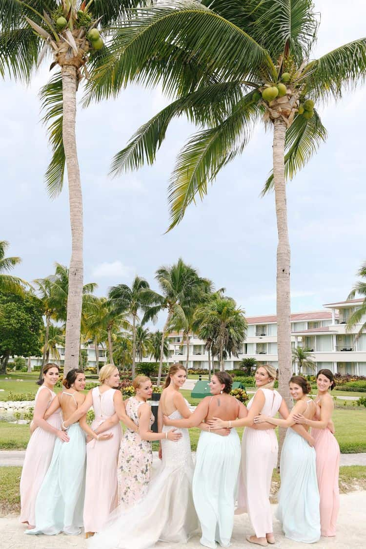 Beach bridal party wearing pastel dresses