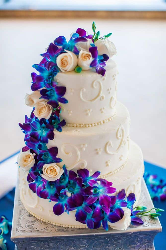 wedding cake with blue and purple orchid flowers