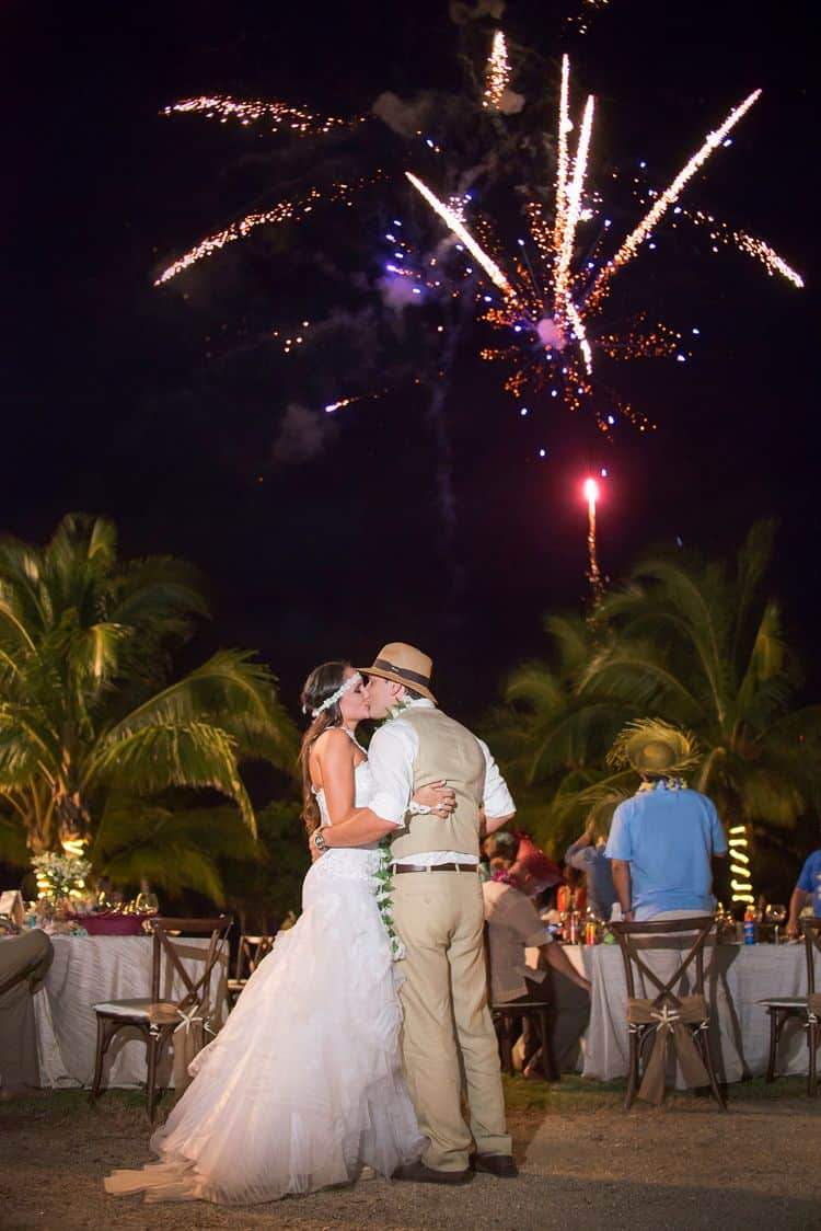Photo of bride and groo with fireworks going off in the background