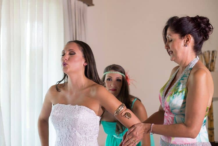 Mother of the bride and bridesmaid helping bride get ready