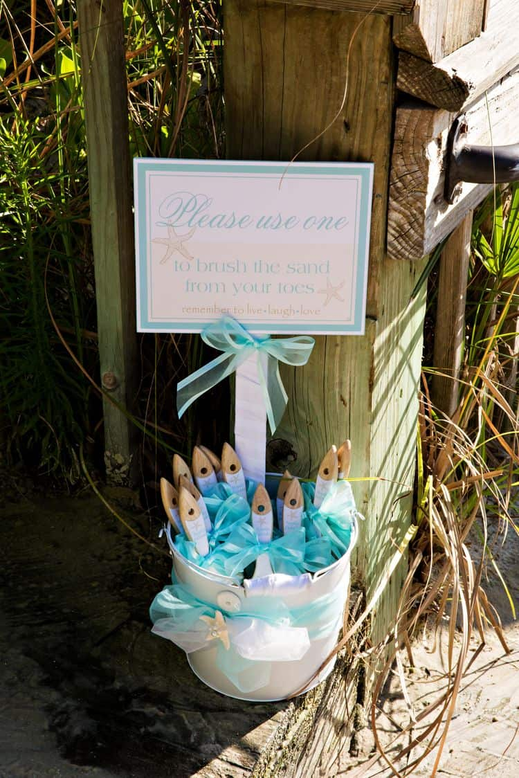 Brushes to remove sand from feet at a beach wedding