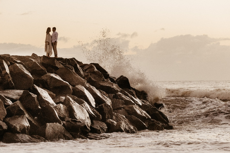 beach wedding photos rock formation crashing waves
