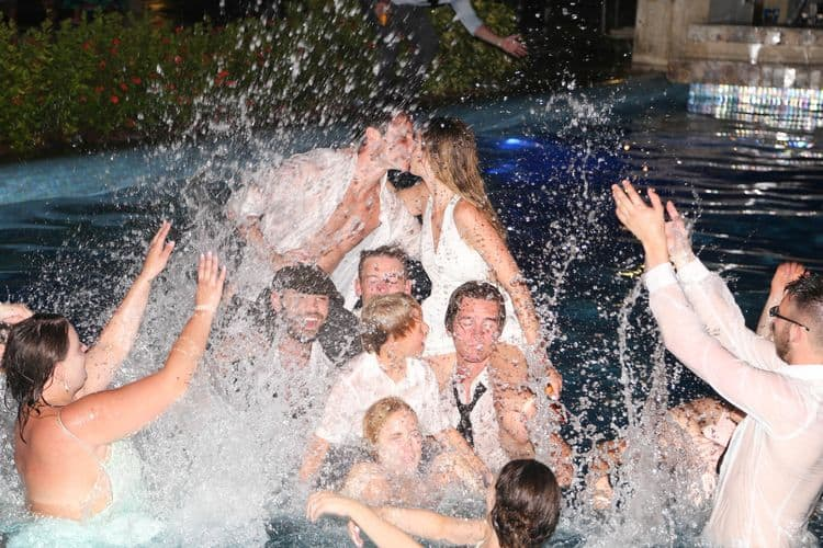 The bridal party jumping into the pool at a destination wedding in Cancun