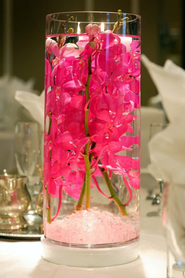 wedding centerpiece with flowers submerged in water with candles